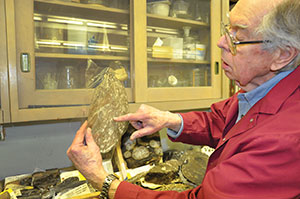 Prof. Emeritus Tom Phillips in the lab inspecting a fossil